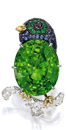 PERIDOT, SAPPHIRE, TSAVORITE GARNET AND DIAMOND 'BIRD' BROOCH Whimsically designed as a bird set with an oval peridot weighing 32.02 carats, the head pavé-set with sapphires and tsavorite garnets, resting on a tree branch pavé-set with circular-cut diamonds, mounted in 18 karat white, yellow and blackened gold.