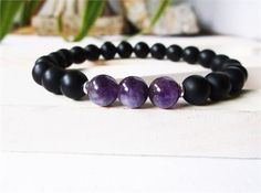 This bracelet is for a man or a woman, made of 8mm classic, matte (non-shiny) black onyx, with genuine 8mm amethyst, and silver accents. This bracelet has a timeless elegance that can easily be worn with a suit or a pair of jeans. This is genuine amethyst; therefore, being a natural stone, it will have a depth of color - from light to deep purple - which will be individual to each stone. The exact color of each stone on a bracelet will be dependent of the specific vein being mined. This…