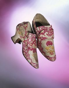 This pair of elegant women's shoes, from Brussels,1760s, is in kid leather with satin covered heel, is beautifully decorated with a painted design. The pattern on the toe, with its flower, vertical lines and scalloped edges, resembles Brussels bobbin lace. The latchets would have been fastened with a buckle. In 1767 Lady Mary Coke recorded in her diary that she had bought six pairs of painted shoes from a shop in Brussels.