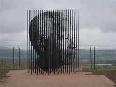 Bel hommage à Nelson Mandela.  50 barres en acier,symbole des barreaux d'une prison, pour ne pas oublier que Mandela a été capturé (pour 27 ans de prison), il y a 50 ans à ce même endroit.  Mais en tournant un peu autour de cette sculpture, à un angle précis, on pourra voir beaucoup plus que de simples barres en acier. (Source anonyme)