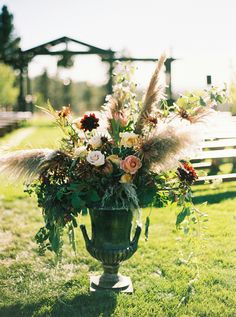 A warm welcome to the ceremony with a mix of cascading florals and feathers