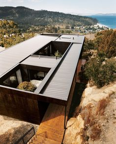 """The Kingston house remains unobtrusive and well camouflaged on its hillside site despite the architects use of modernist geometry. The outer cladding is simply plywood stained with dark Madison oil."" See full story on Dwell.com  Architecture: Aaron Roberts Room11 Thomas Bailey  Photo: Andrew Rowat #dwell #architecture"