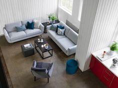 Harmaasävyisen olohuoneen sohvakalusteissa on aavistus retrohenkisyyttä…