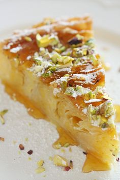 Greek Bougatsa with Honey and Pistachios Dream layers of flaky phyllo dough are filled with a vanilla custard and topped off with pistachios and honey for a new take on an elegant Greek pastry. Greek Sweets, Greek Desserts, Just Desserts, Delicious Desserts, Yummy Food, Greek Food Recipes, Lebanese Desserts, Greek Pastries, Greek Cooking