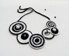 This unique necklace is hand crocheted with black and white cotton thread and beaded with irregular shaped mother of pearl beads.  Circles measure between 4,2 cm - 7,5 cm in diameter   This necklace can be tied in a simple bow at the back, I have left this long so that you can decide the length.   All my pieces are made from the heart and carefully handcrafted with attention to detail from start to finish in a smoke free environment.