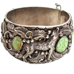 Navajo Wolf Cuff. Vintage signed N sterling Navajo wolf cuff featuring a lovely green turquoise with matrix. The wolf even has visible teeth. I have seen similar motifs before in Navajo works, but not with the green turquoise. The piece was made for a man, but later customized by the former owner with a Mexican made clasp. This stylized and signed Hecho en Mexico, Novoa latch was made to close the piece securely for wear.