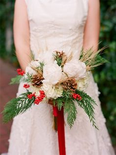 Stunning evergreen, pine cone, red berry and white flower bouquet that would look beautiful as a Christmas table centerpiece.