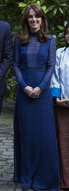 Catherine, Duchess of Cambridge dazzled at Kensington Palace this evening in a gorgeous navy Saloni maxi dress. This elegant long dress has a Victorian vibe to the style with long sheer polka dot bell sleeves and a high ruffle neck. And in a slightly daring look it features a sheer plunge neckline