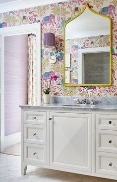 Colorful elephants and camel wallpaper livens a kids' bathroom lit by nickel sconces paired with purple shades and mounted on either side of a gold vanity mirror. Boho Bathroom, Bathroom Kids, Bathroom Styling, Bathroom Interior, Bathroom Lighting, Small Bathroom, Gold Vanity Mirror, Purple Mirror, White Vanity