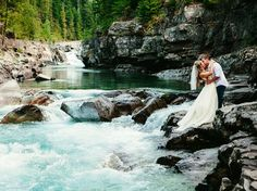 bride and groom embrace on river bank