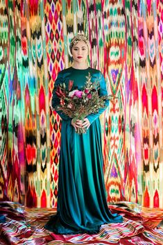 Uyghur bride. Vibrant  traditional atlas (ikat) fabric background. The Uyghurs hail from Central Asia, Turkic in ethnicity but residing in North Western China in a region referred to as East Turkestan.