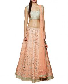 Peach Lehenga with resham embroidery comprising a sage green choli with gota patti and dori work, and resham embroidery all over. Featuring a scoop neckline with a princess panel design. Cap sleeves. Sage green piping details at the neckline, cuffs and hemline. Cut out back design with drawstrings detailed with beads. This Lehenga set comes with a peach Lehenga skirt detailed with gota patti, dori and resham embroidery. Golden and sage green border with gota patti and dori work.  Wash Care…