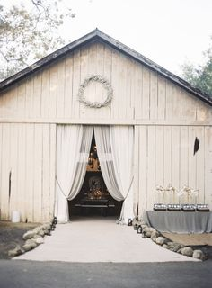 Flowy white drapes dress up the entrance to this barn. Love this!