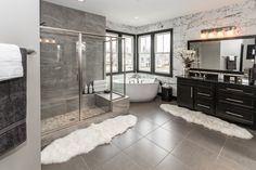 You'll love the luxurious master bathroom in this new home with a floor to ceiling tiled walk-in shower with glass doors, free standing bath tub, and large vanity. Seen in the Wheatland at Thorpe Creek located in Fishers, IN. | Fischer Homes