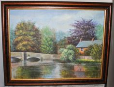 Framed Painting on Canvas of House by the River and a Bridge, Signed Mark Davies