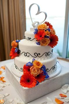 Navy and coral wedding cake with an elegant heart topper