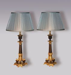 A pair of early Century bronze and ormolu Candlesticks, having leaf carved nozzles, above triform tapering stems, raised on leaf and scroll supports, ending on decorated triform bases.(Now converted to lamps.) Height with Shade: Circa: 1830 Ref: 5698 Candlestick Lamps, Candlesticks, Lantern Chandelier, Lanterns, Stems, Antique Furniture, Wall Sconces, 19th Century, Table Lamp