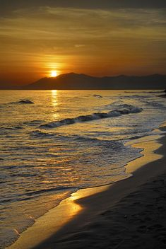 Love the beach with the sun barely setting behind the mountains truly a beautiful scene!