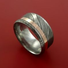 This 10mm wide DAMASCUS ring has a 2mm Off Center, inlaid with a deep 14K ROSE GOLD TEXTURED DULL FINISH. Each ring is custom made and the pattern unique, so no two rings are exactly alike. Damascus S