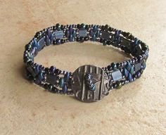 I love the slinky, sleek feel of this beautiful bracelet. I have combined rich colors of deep purple, marine blue, black and gunmetal for a distinctly elegant look. This lovely design by Ramona Brummett uses a variety of shaped glass beads. I used 2-hole square Myiuki Tilas, superduos, and Toho seed beads. It is finished with a button loop clasp featuring a gunmetal button made by TierrCast.  This piece measures 7 1/4 inches long so it will fit up to a 6 1/2 inch wrist nicely.  Your bracelet…