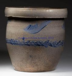 """DECORATED STONEWARE CROCK, salt glazed, approximately two-gallon capacity, classic semi-ovoid wide-mouth form with two incised medial rings and a heavy overhanging broad squared rim. Brushed cobalt feathered wing decoration below rim and medial laurel-leaf band following incised rings. The circle of Andrew Coffman, probably John D. Heatwole and/or Emanuel Suter, Dry River; possibly one of Andrew Coffman's sons working at Dry River or the Beldor area. Circa 1850-1860. 9"""" H, 9"""" D rim…"""