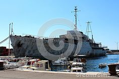 Old large historic rusted and beaten down ship called Galeb docked in harbor in Rijeka, Croatia. Waiting patiently for restoration and better days while being available for tourists and explorers.