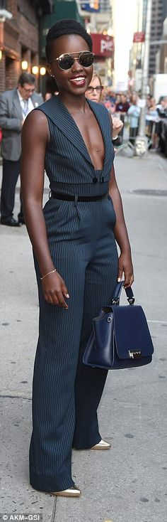 The beauty's metallic heels were just visible under her trouser leg, and she carried a box-style dark blue bag