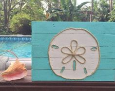 This beachy piece of art is made from reclaimed pallet wood and is perfect for a nautical inspired beach house! Each sign is hand cut, hand sanded and hand painted. Each sign is made to order so no two will be exactly alike due to variations in the wood. All signs have cable wire on the back for easy hanging. Dimensions are approximately 16 x 16.