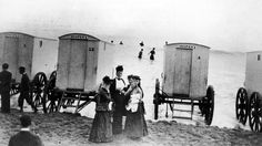 Victorians at an English seaside with bathing huts already prepared to preserve their modesty.