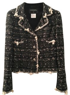 Chanel classic black and white tweed jacket. This jacket features black and white fantasy tweed with fringed details. Unique silver buttons have 5 cute little Chanel logos on it. This is a classic timeless piece to own. Size 34.