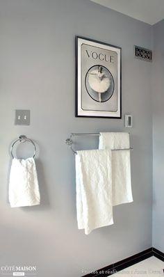 Des porte-serviettes gris métalliques accompagnés d'un petit tableau décoratif au-dessus.