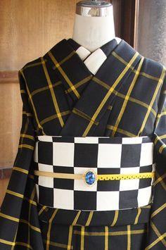 シックな黒の地に繊細なラメ糸で縁取られたシンプルモダンなイエローチェックが織り出されたウールの単着物です。