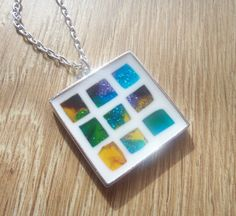 Unique resin mosaic pendant, made with handmade resin tiles in transparent shades of shimmery blue, green, purple and yellow on a white resin