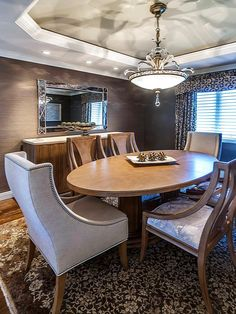 This transitional dining room is designed using clean modern furnishings with a touch of traditional style. The draperies are a classic style made more modern by the silk and velvet scroll fabric. The finishing touch to this room is the modern take on a traditional chandelier. The cut crystals in a warm muted silver-leaf finish adds the perfect glow.