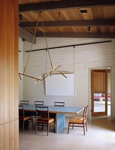 The custom lighting fixture and the dining table were both designed by De Lisle