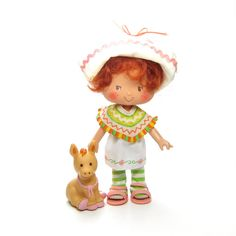 This vintage Strawberry Shortcake doll is Cafe Ole with her pet donkey, Burrito. Cafe Ole is one of Strawberry Shortcake's International Friends. She has brown eyes and short reddish hair with loose c