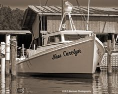 """""""The old deadrise work boats. The Miss Carolyn is a beauty, and I liked the way she was sitting here with the dark sky and rusted tin roof of the boat shed."""" RC Norman, Photographer. Who was Miss Carolyn? Why was a boat named for her? Beauty against the rust. What's her story?"""