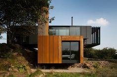Patrick Bradley Architects est une studio d'architecture basé en Angleterre et en Irlande, spécialisé dans la rénovation et la construction contemporaine.  Cette habitation réalisée avec 4 containers de fret est la première du genre en Irlande du nord. Sur deux niveaux, cette habitation joue avec les lignes géométriques et rectilignes des containers qui la composent. Le module du haut sert d'espace de vie et est peint en gris métal, tandis que les volumes du bas sont traités en acier corten.