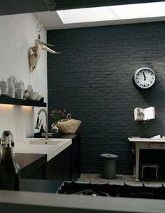 Cocina. Tiene pisos de cemento alisado que combinan con las paredes de ladrillo pintadas de color gris oscuro y muebles bajo mesada en negro, colocados sobre una pared que se pintó de blanco. La mesa es también de color oscuro y la acompañan unas sillas Tolix, de diseño francés en estilo industrial vintage.