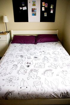 I love this idea! This momma saved her son's artwork, photographed it, turned it black and white, increased the size, and traced it onto a plain white duvet cover.