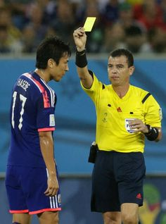 Japan's Makoto Hasebe, left, is booked by referee Joel Aguilar from El Salvador during the group C World Cup soccer match between Japan and ...