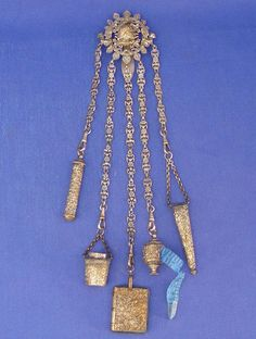 VICTORIAN SEWING CHATELAINE: European design pendant with 5 sewing accessories on ornate chains. needle holder, thimble, pin cushion (book shape), tape measure and scissor holder. Chains vary in length from 4 to 7 1/2 in length. Silver over metal.