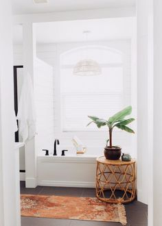 A white, bright, master bathroom with shiplap detail and gorgeous Delta Trinsic Collection faucets in matte black. Bohemian Master bathroom on a budget. #Ad