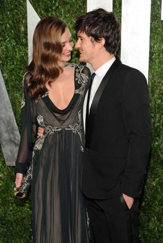 Miranda Kerr wore a Valentino silk gown, styled with glamorous side swept curls, a Jimmy Choo clutch and a slick of red lipstick, to attend the Vanity Fair party with husband Orlando Bloom - who wore a Saint Laurent tuxedo.