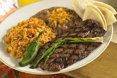 Carne Asada steak with refried beans, rice, and tortillas
