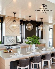 Transitional kitchen design with light wood cabinetry and black upper cabinetry. Leather bar stools and glass pendants above island. Wood Kitchen Cabinets, Kitchen Dining, Kitchen Decor, Kitchen Flooring, Dining Rooms, Kitchen Island, Luxury Kitchens, Cool Kitchens, Beach Kitchens