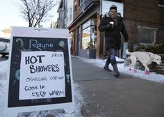 A man walks his dog past a spa advertising free hot showers for residents whose electricity remains knocked out by an ice storm, on Danforth Avenue in Toronto December REUTERS/Chris Helgren Ice Storm, Hottest Photos, Past, Toronto, Advertising, Canada, Walks, Showers, December