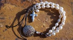 Nouvelle Pearl and Leather Bracelet by fleurdesignz on Etsy I like the use of the pearls with the leather and the cross dangle with the button closure. csa