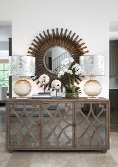 A mirrored buffet with decorative curved wood trim is dressed with glass orbs…