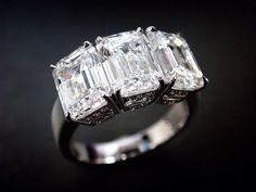 One-of-a-kind elegance, this diamond ring features three stones of emerald cut…
